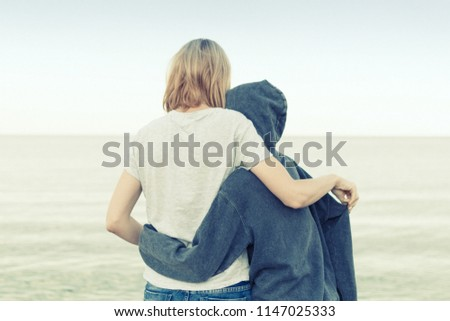 Mutual understanding between the parent and the child. Mother and daughter teenager embrace on the seashore, ocean.