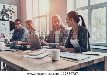 Mutual understanding. Group of young modern people in smart casual wear discussing business while working in the creative office