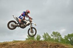 MX racer lands on the front wheel on the hillside