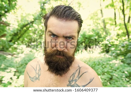 My beard my look. Unshaven hipster with textured beard hair on summer nature. Bearded man with stylish mustache and beard shape. Serious caucasian guy with beard on natural landscape.