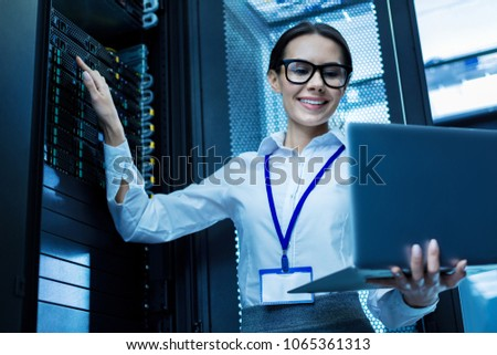 My best day. Content attractive woman working in a server cabinet and holding her laptop Zdjęcia stock ©