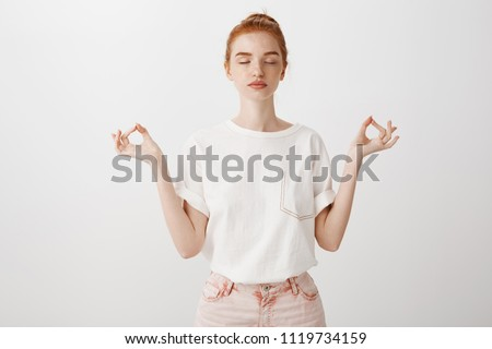 My body is fortress. Calm fashionable young european woman with ginger hair, standing with closed eyes and relaxed expression, spreading hands in zen gesture, meditating and practicing yoga