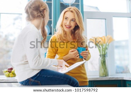 My dear child. Beautiful cheerful blond slim mother smiling and holding a cup of tea and her daughter using a tablet while sitting on the table #1017598792