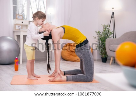 My dear mom. Young athletic mother doing some exercises with her daughter while standing on the carpet #1081877090