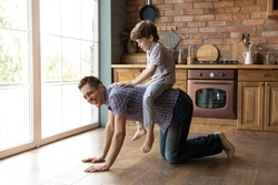 My favorite horse. Laughing millennial father and little kid son playing active games at home having fun. Young dad crawling on all four by warm kitchen floor and excited child boy riding on his back
