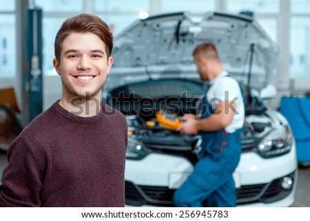 My favorite service station. Portrait of a handsome male client smiling while standing in the car repair station with a car mechanic checking his auto on the background