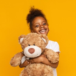 My favorite toy. Cute little african girl hugging her teddy bear and smiling, orange studio background