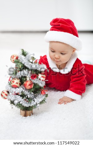 My first christmas - baby girl in santa outfit with small decorated tree