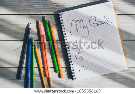 My Goals written in a notebook with assorted colored pencils on wooden table, top view