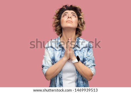 My god please help me. Portrait of hopeful young woman with curly hairstyle in casual blue shirt standing with palm hand and praying or begging. indoor studio shot, isolated on pink background.