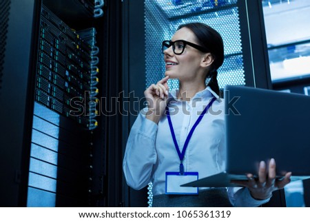 My good day. Alert beautiful woman working in a server cabinet and holding her laptop Zdjęcia stock ©