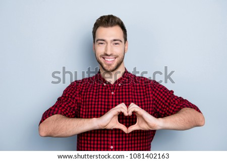 My heart belongs to you! Portrait of excited in love sensual tender gentle cute with toothy smile guy wearing red checkered shirt imitating heart using his hands, isolated on gray background