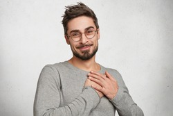 My heart is for you! Pleasant looking male model with appealing appearance demonstrates his positive emotions and feelings to people whome he truly loves, has pleased and friendly expression