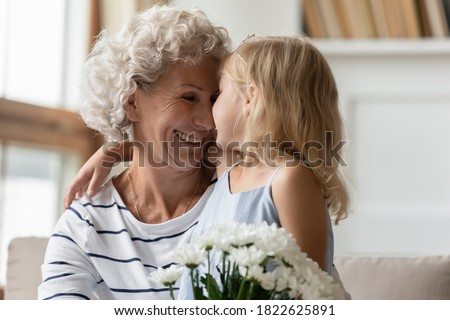My little princess. Loving attentive little granddaughter congratulating happy mature hoary granny with birthday or Women Day cuddling her, tender looking in eyes and presenting bouquet of flowers