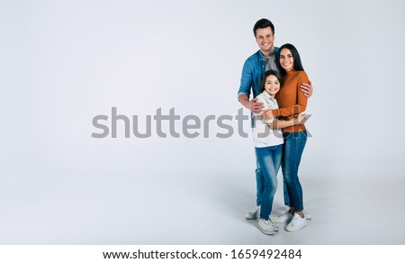 My precious family. Full-length photo of a family of three people standing together, looking in the camera and smiling.