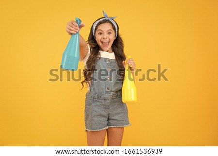 My reputation is spotless. Happy little girl hold household cleaning products. Small child smiling with household spray bottles. Enjoying household activities. Providing household help, copy space.