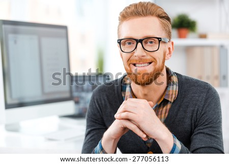 My space to create. Handsome young bearded man in eyewear looking at camera and smiling while sitting at his working place - Shutterstock ID 277056113