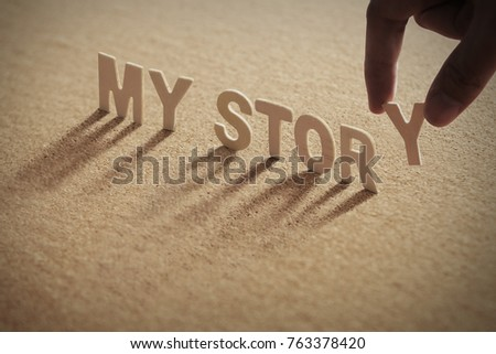MY STORY wood word on compressed or corkboard with human's finger at Y letter.