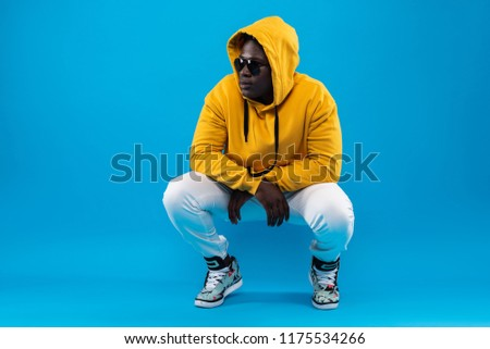 My style. Studio portrait of young man in yellow hoodie hunkering down and looking away with calm expression Stockfoto ©