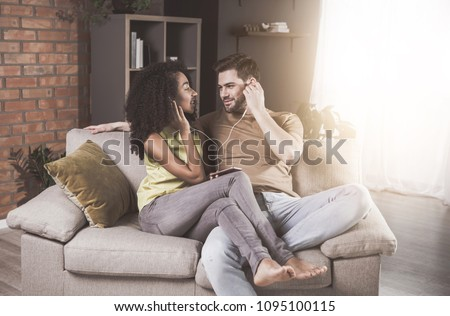 My sweetheart. Young enamored husband is sitting on cozy couch with his gorgeous wife. They are enjoying favorite songs using earphones on mobile phone. They are looking at each other with adoration
