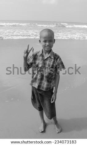 Myanmar, Ngwesaung beach, November 05, 2014. Fun cute boy on the beach. Black and white.