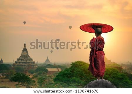 Myanmar Novice monk holding umbrella standing on the pagoda watching pagoda in Bagan sunrise morning time of Bagan Mandalay Burma