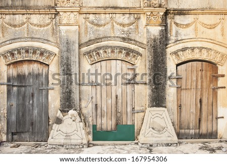 Myanmar travel and people images.Three old wooden doors in exterior wall of Burmese pagoda. Myanmar travel and people images.