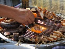 Myanmar typical street food, pork offal skewers dipping in hot soup at Uben bridge. Burma November 2013.