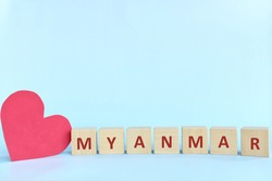 Myanmar word on wooden blocks with red heart shape cutout in blue background. Support, sympathy pray, and send love to Myanmar concept.