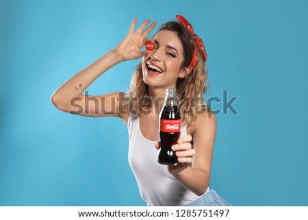 MYKOLAIV, UKRAINE - NOVEMBER 28, 2018: Young woman with bottle of Coca-Cola and cap on color background #1285751497