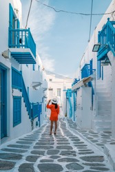 Mykonos Greece, happy Young girl on vacation in Mikonos walking in town with red dress