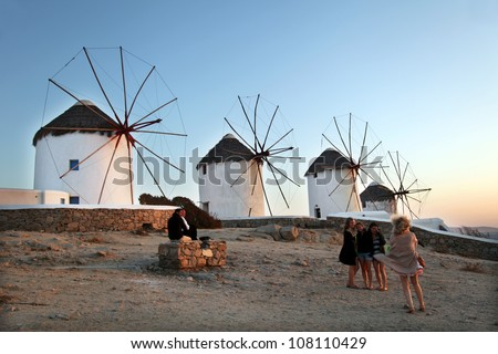 MYKONOS, GREECE - JUNE 29: Group of people posing in front of a windmill on June 29, 2012 in Mykonos, Greece. Windmills from the 16th century, they are one of the most recognized landmarks of Mykonos.
