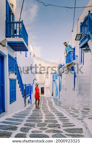 Mykonos Greece, Young man and woman in dress at the Streets of old town Mikonos during a vacation in Greece, Little Venice Mykonos Greece. couple mid age vacation Greece