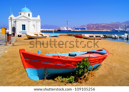 Mykonos harbor with old boat and blue dome church, Greece