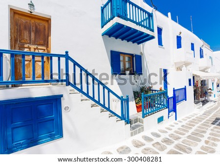 Mykonos old town street with cobbled walkways, white walls, and painted door and windows, Mykonos island, Greece