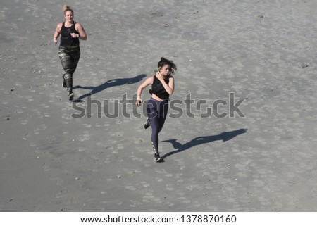 Myrtle Beach, SC/United States- 04/16/2019: 2 young ladies race each other on the beach.
