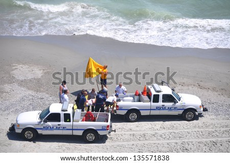 MYRTLE BEACH, SOUTH CAROLINA - APRIL 18 - Paramedics, Beach Police, Lifeguard work together to load unidentified drowning victim for transport to hospital at Myrtle Beach on the 18th of April 2013.