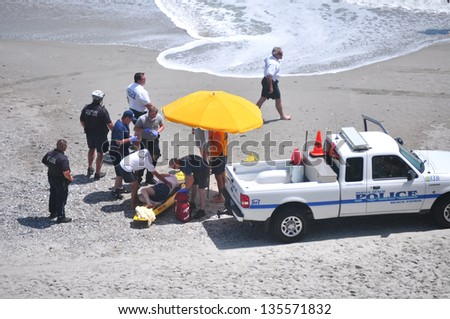 MYRTLE BEACH, SOUTH CAROLINA - APRIL 18 - Paramedics, Beach Police, Lifeguard work together to save unidentified drowning victim at Myrtle Beach on the 18th of April 2013