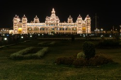 Mysore Palace illuminated by thousands of lightbulbs in the background. The /garden in the foreground. Mysore, Karnataka, India