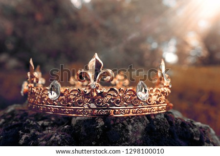 mysterious and magical photo of gold king crown over the stone covered with moss in the England woods or field landscape with light flare. Medieval period concept. Toned and filtered