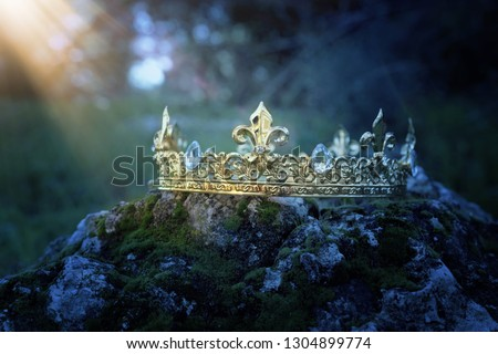 mysterious and magical photo of gold king crown over the stone covered with moss in the England woods or field landscape with light flare. Medieval period concept