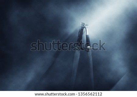 mysterious and magical photo of silver sword over gothic black background with smoke. Medieval period concept