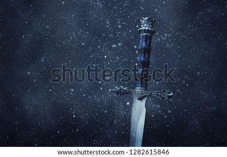 mysterious and magical photo of silver sword over gothic snowy black background. Medieval period concept