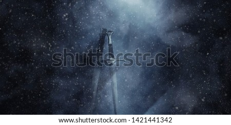 mysterious and magical photo of silver sword over gothic snowy black background. Medieval period concept #1421441342