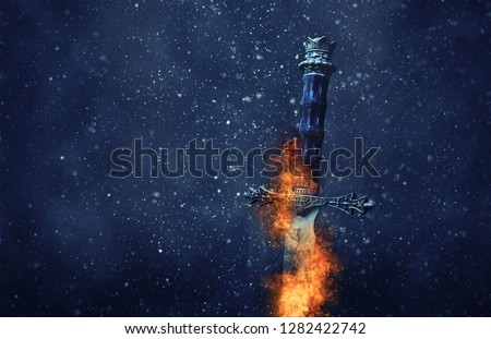 mysterious and magical photo of silver sword with fire flames over Gothic snowy black background. Medieval period concept