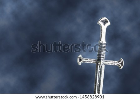 Mysterious and megical medieval sword / knightly arming sword, silver straight blade, double-edged weapon, single-handed, cruciform (cross-shaped) hilt. Gothic black background with scattering smoke