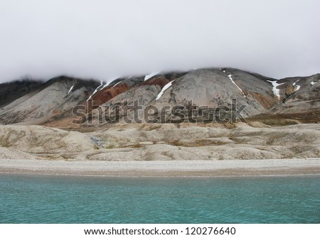 Mysterious arctic view - blue waters of Recherchefjorden and barren shore with melting snow and heavy fog, Spitsbergen archipelago (Svalbard island), Norway, Greenland Sea, Atlantic ocean