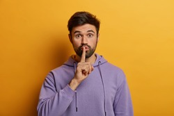 Mysterious bearded young man makes shush gesture, asks to keep secret safe, says keep voice down, quiet please, touches finger over lips, dressed in purple hoodie, isolated on yellow background