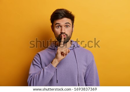 Photo of  Mysterious bearded young man makes shush gesture, asks to keep secret safe, says keep voice down, quiet please, touches finger over lips, dressed in purple hoodie, isolated on yellow background