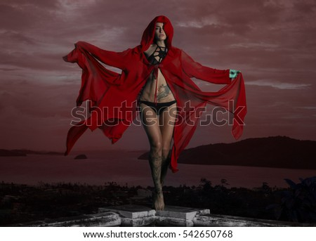 Mysterious beautiful woman in black crochet bikini and red hoody cover up posing in wind over cloudy sky and cityscape - Shutterstock ID 542650768